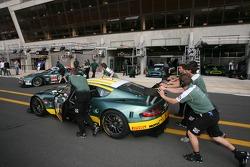 Aston Martin Racing team members push their car on pitlane
