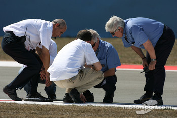 Track workers and the FIA try to repair a drain cover which came loose during the session