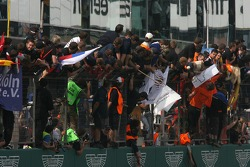 Team members and drivers celebrate at the pitwall as the cars cross the finish line