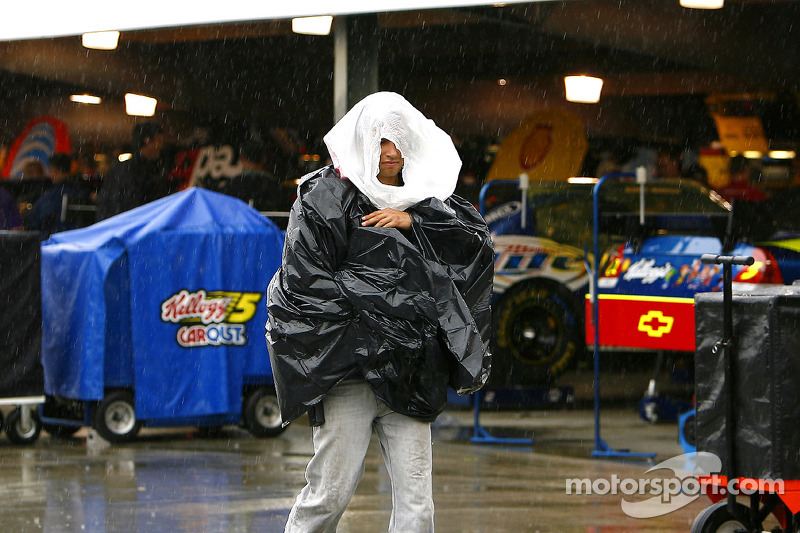 A photographer uses garbage bags as makeshift rain gear as he prowls the garage at Martinsville
