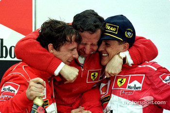 Podium: race winner Michael Schumacher and second place Eddie Irvine celebrate with Jean Todt