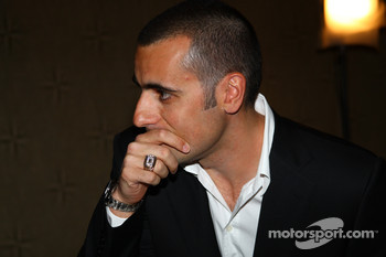 Dario Franchitti, wearing his Champion of Champions winner's ring, admires his image on the Borg-Warner Trophy during the Shav Glick Newsmakers Forum