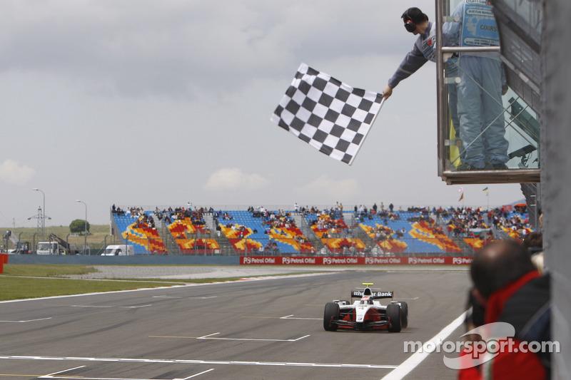 Romain Grosjean crosses the line to take victory