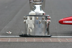 An orchid from the winner's wreath sits on the track next to the Borg Warner Trophy and the nose of Scott Dixon's car