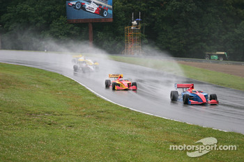 Cars try to negoiate a slick track and heavy rain