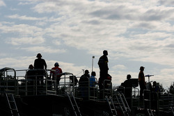 Crew chiefs stand atop their haulers as they watch the cars practice