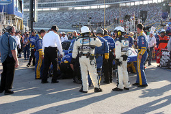 A crowd gathers behind the wall as Kevin Harvick's crew attempt to repair the car