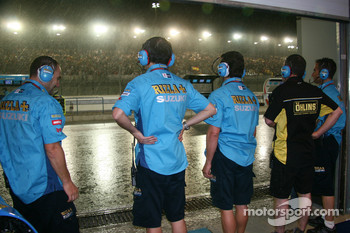 Rizla Suzuki MotoGP team members look on as a rainstorm falls on Losail International Circuit