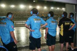 Rizla Suzuki MotoGP team members look on as a rainstorm falls on Losail International Circuit