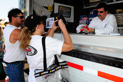 NASCAR President Mike Helton signs autographs for fans