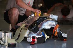 A McLaren mechanic working on a seat