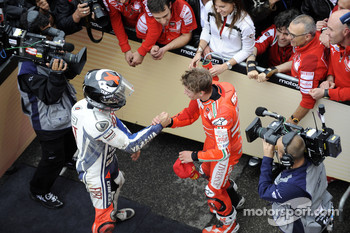 Race winner Casey Stoner is congratulated by second place Jorge Lorenzo