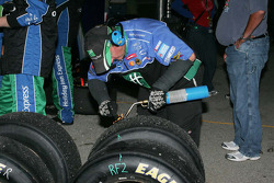 A crew member for Stephen Leicht cleans tires