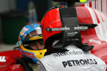 Michael Schumacher, Mercedes GP talks to Fernando Alonso, Scuderia Ferrari