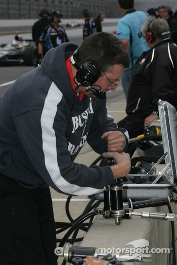 A crew member for A.J. Foyt Enterprises works on shocks