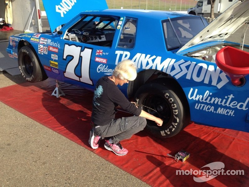 Ellie Cesario checks tire pressures on the #71 Dave Marcis NASCAR Historic 1979 Oldsmobile