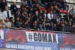 A large group of Max Verstappen, Red Bull Racing, supporters sit above a banner in the grandstand