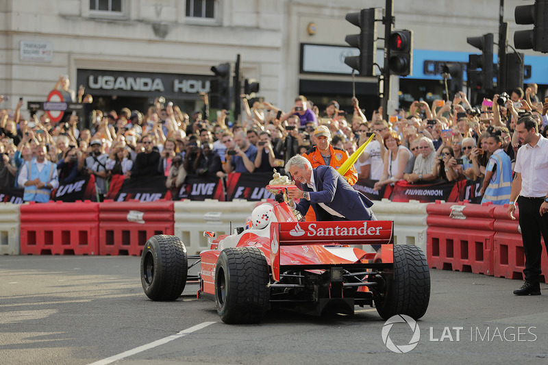 Дженсон Баттон з Наомі Кемпбелл у двомісному боліді Ф1 поряд з Деймоном Хіллом, котрий тримає кубок за перемогу у Гран Прі Великої Британії