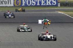 Un homme court devant les voitures en piste