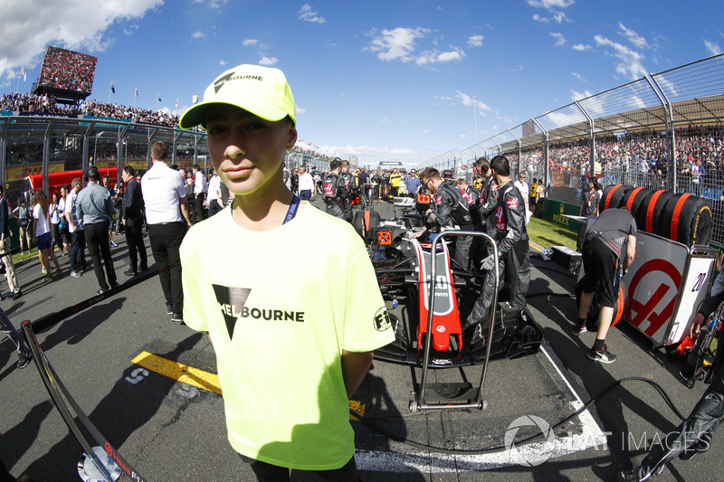 A Melbourne grid mascot stands in front of the car of Kevin Magnussen, Haas F1 Team VF-18 Ferrari