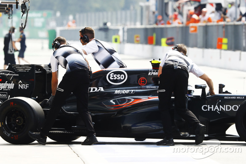 Jenson Button, McLaren is wheeled back into the garage in the pit lane