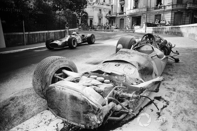 1968年モナコGP:大破したペドロ・ロドリゲスのBRM P133の横を抜けていく、デニス・ハルム(マクラーレン・コスワースM7A)
