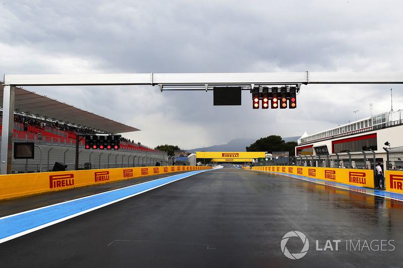 Rain pours down on an empty track below a light gantry