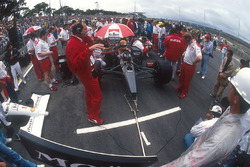 Ayrton Senna, McLaren MP4/6 Honda, sits in pole position on the grid, with team boss Ron Dennis and chief designer Neil Oatley in front