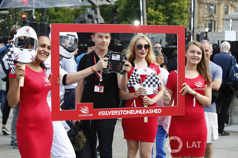A young fan has his photo taken, some Grid Girls