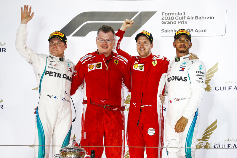Valtteri Bottas, Mercedes AMG F1, 2nd position, Sebastian Vettel, Ferrari, 1st position, and Lewis Hamilton, Mercedes AMG F1, 3rd position, on the podium with the Ferrari team member who collected the Constructors trophy