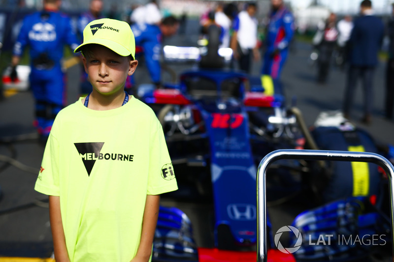 A Melbourne grid mascot in front of the car of Brendon Hartley, Toro Rosso
