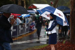 A member of the Williams team shelters from the rain under an umbrella