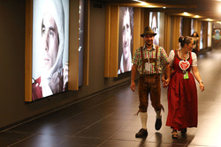 Traditionally dressed fans walk past a gallery of world champions