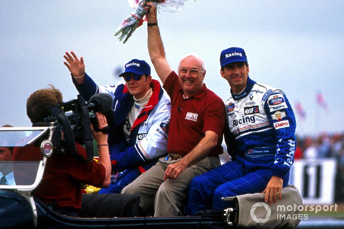 BBC Grand Prix commentator Murray Walker waves to the crowds. Beside him are Rothmans Williams drivers Damon Hill and Jacques Villeneuve