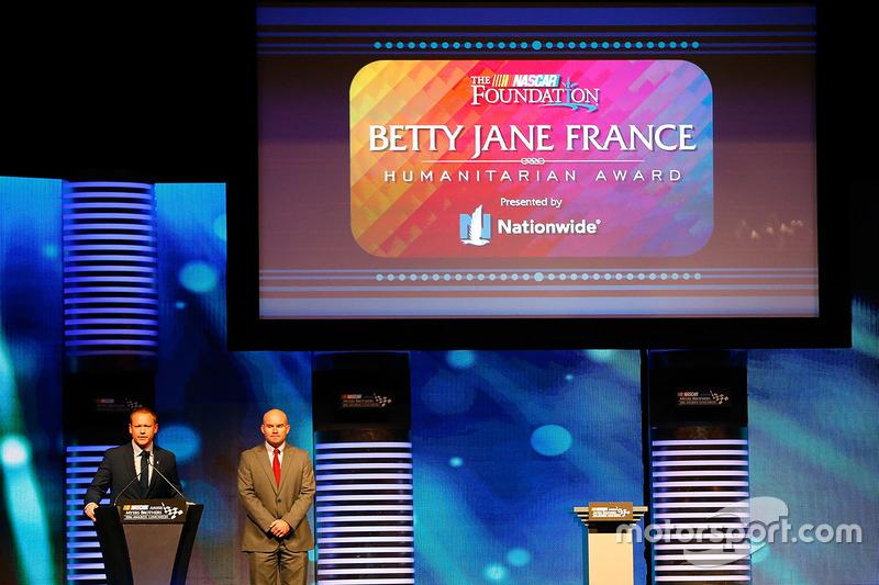 Brad Barnett, vicepresidente asociado de medios nacionales y marketing deportivo para todo el país, Andy Hoffman antes de obtener el premio humanitario Betty Jane France presentado por Nationwide durante el almuerzo de premios NASCAR NMPA Myers Brothers