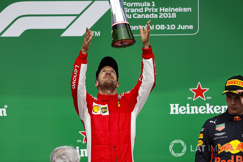 Sebastian Vettel, Ferrari, 1st position, tosses his trophy into the air in celebration on the podium