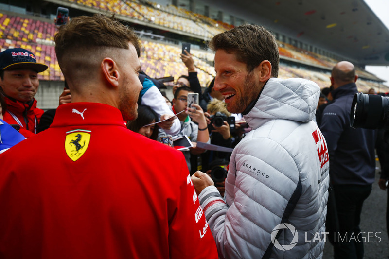 Romain Grosjean, Haas F1 Team, talks to Sebastian Vettel, Ferrari