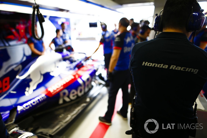 A Honda team member works in the Toro Rosso garage