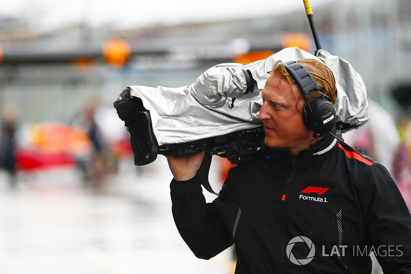 An F1 TV Cameraman with his equipment protected from the rain