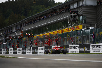 Sebastian Vettel, Ferrari SF71H, takes the chequered flag at the finish, and the applause of his team on the pit wall
