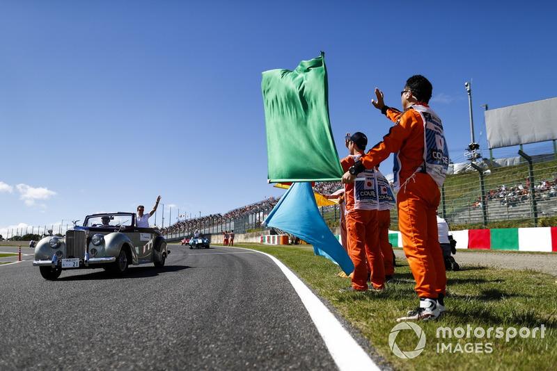 Los comisarios ondean las banderas al paso de Stoffel Vandoorne, McLaren