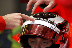 A mechanic points to some damage on the visor of Max Chilton, Marussia F1