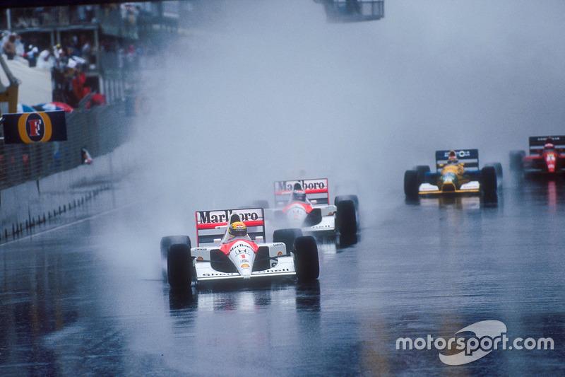 Ayrton Senna leads teammate Gerhard Berger, both McLaren MP4/6 Honda's, Nigel Mansell, Williams FW14 Renault, behind Berger's car in spray, Nelson Piquet, Benetton B191 Ford, and Jean Alesi, Ferrari 643, at the start