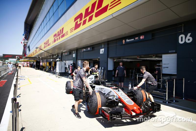 Dei meccanici Haas spingono la monoposto di Kevin Magnussen, Haas F1 Team VF-18