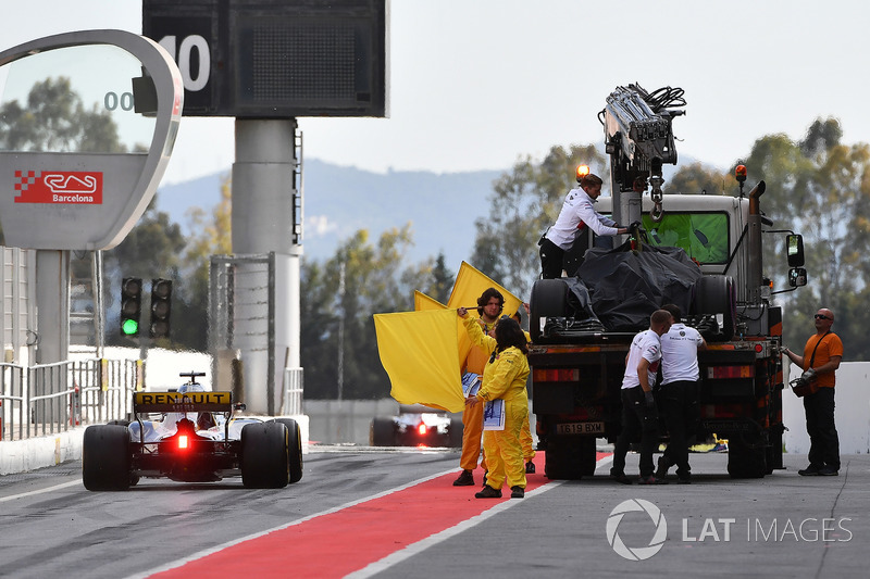 Marshals wave yellow flags in pit lane