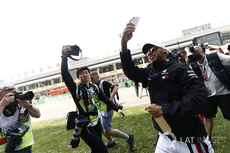 Lewis Hamilton, Mercedes AMG F1, is mobbed by photographers, as he takes a picture of fans with his