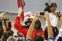 Team members capture the arrival of Sebastian Vettel, Ferrari, 1st position, in Parc Ferme