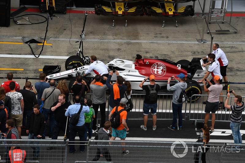 La Sauber C37 dans la pit lane avec des fans