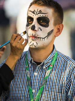 Day of the Dead-style face paint is applied to members of the paddock