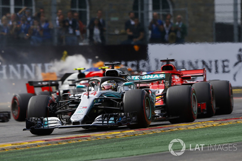 Lewis Hamilton, Mercedes AMG F1 W09, leads Sebastian Vettel, Ferrari SF71H, and the remainder of the field as Fernando Alonso, McLaren MCL33, crashes out in the background